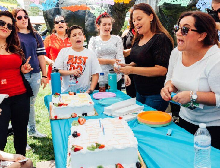 Justin Favela's family sings around 2 cakes