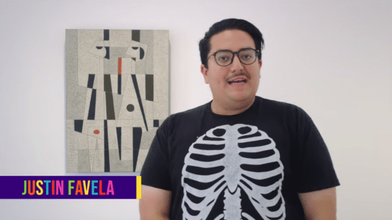 Justin Favela stands in front of a painting